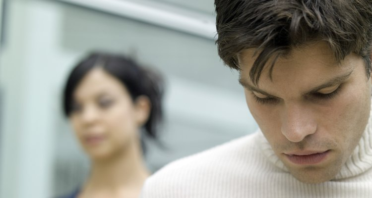 Young man looking down and a young woman behind him