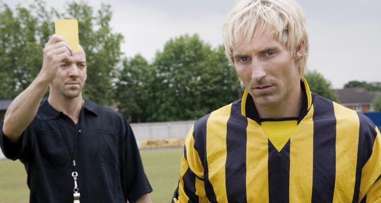 Os árbitros distribuem cartões amarelos para acautelar jogadores de futebol
