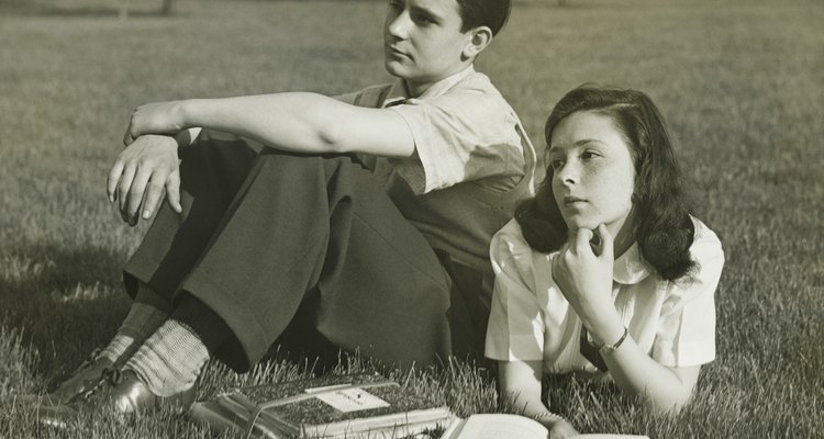 Two teenagers resting in field, boy (16-17) sitting, girl (14-15) lying with book, (B&W)