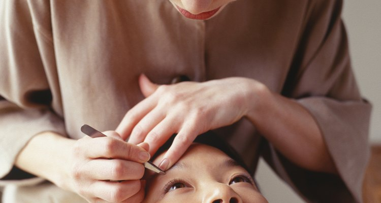 Young woman having eyebrows plucked at beauty parlour
