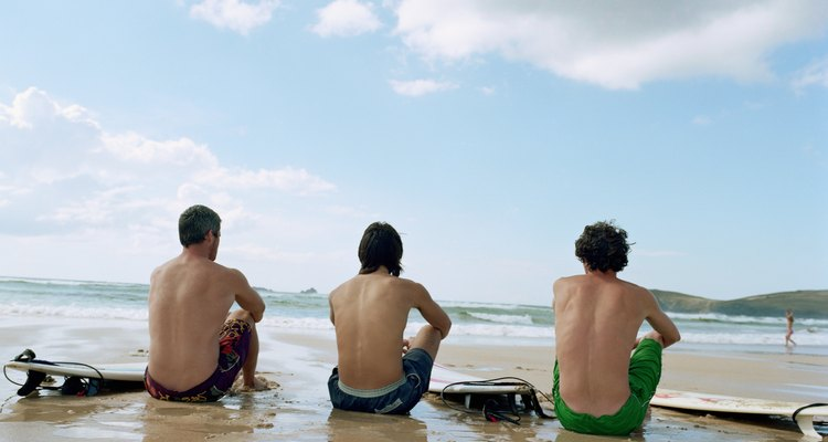 Three men sitting on wet sand by surfboards, rear view