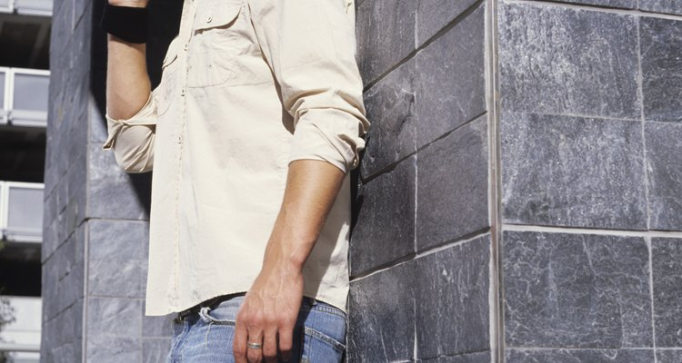 Young man leaning on wall using mobile phone, side view