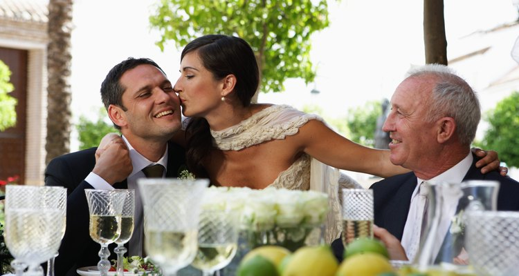 Bride kissing groom at table by father