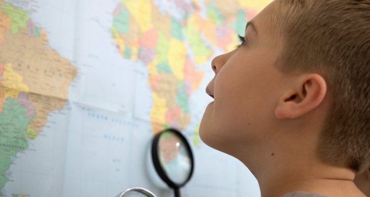 Boy (6-8) looking at atlas, close up, low angle view