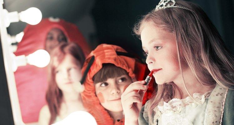 Two girls (5-8), one watching friend applying lipstick in stage mirror