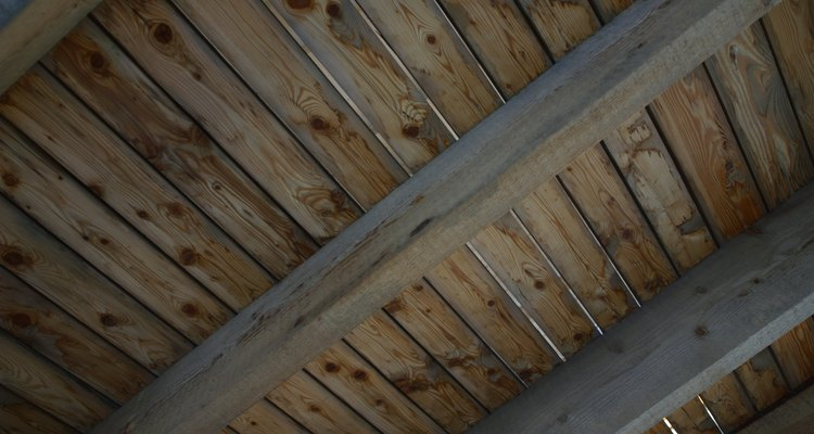 Un diseño de techo estriado con lengüeta entrelaza tablas de madera de pino para crear un patrón en el techo con un estilo de viejo mundo.