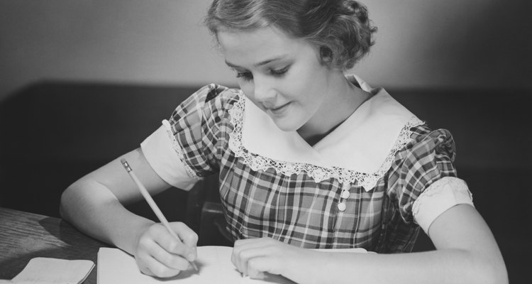 Young girl (12-13) at table doing schoolwork, (B&W)