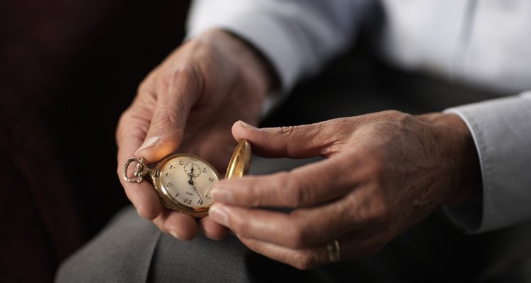 Senior man holding old pocket watch, mid section, close-up of hands