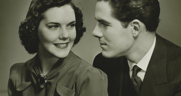 Couple looking in eyes, posing in studio, (B&W), portrait
