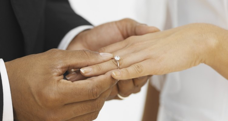 close-up of a groom putting a ring on his bride's finger