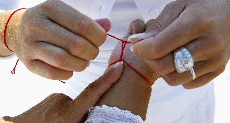 Mulheres israelitas francesas usam seus braceletes de fio vermelho da Cabala enquanto oram em Jerusalém