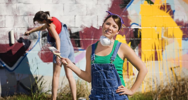 Workers paint over graffiti to demonstrate socially responsible commitment to the community.