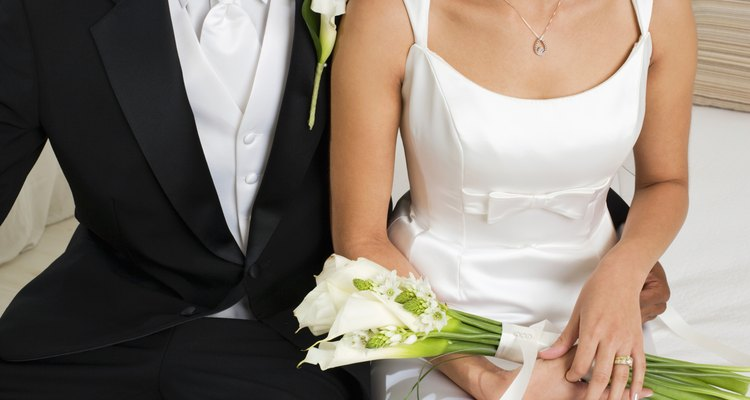 Bride holding bouquet beside groom