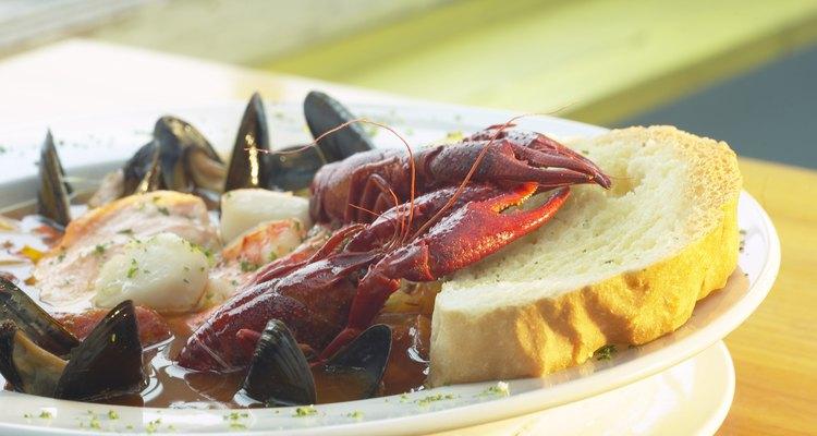 Uma tigela de lagosta, camarão, vieiras e mexilhões em um caldo com uma fatia de pão