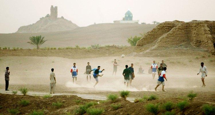 Una antigua torre zigurat babilónica se vislumbra detrás de un moderno campo iraquí de fútbol.