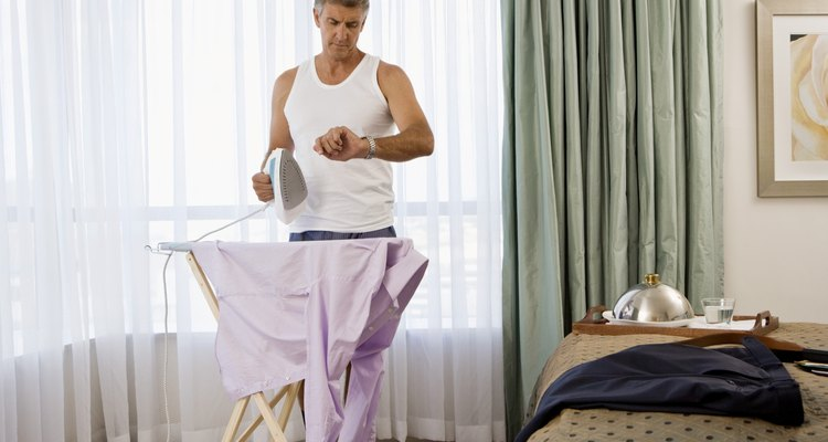 Businessman ironing shirt and checking watch