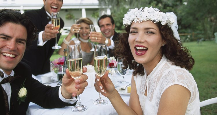 Portrait of a newlywed couple and wedding guests toasting with champagne