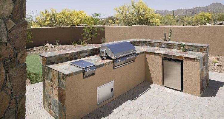 Una cocina al aire libre con parrilla incorporada, armarios y un mini refrigerador.