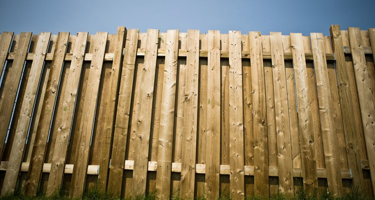 Clean your wooden fence once a year to maintain its appearance.