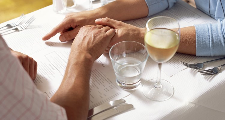 Gay couple holding hands in restaurant