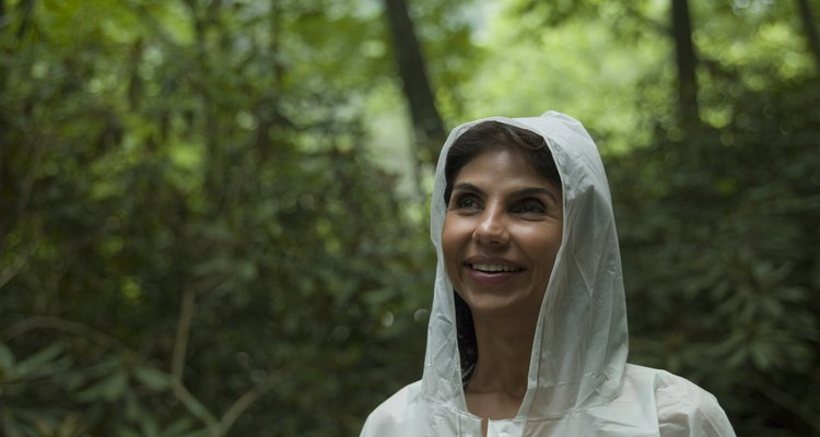 Close-up of mature woman in white raincoat, smiling