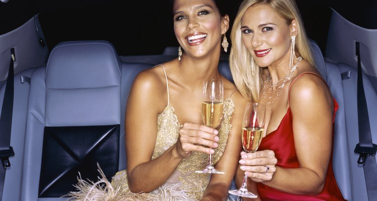 Famous, successful women celebrating in limousine
