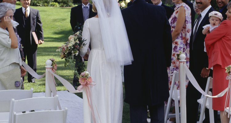 Bride and father walking down aisle at out door wedding ceremony
