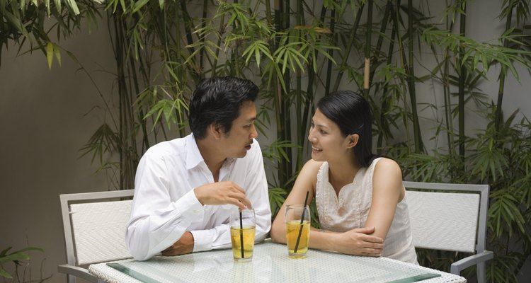 A Vietnamese couple having cold drinks on an outdoor patio.