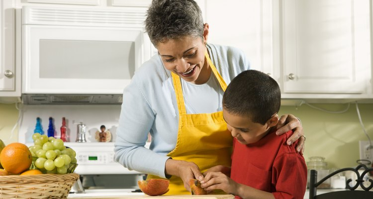 Grandmother and grandson cooking in kitchen