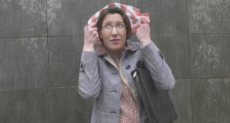 Businesswoman standing in rain holding plastic bag over head