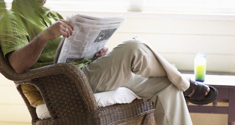 Mature man sitting on wicker rocking chair, reading newspaper