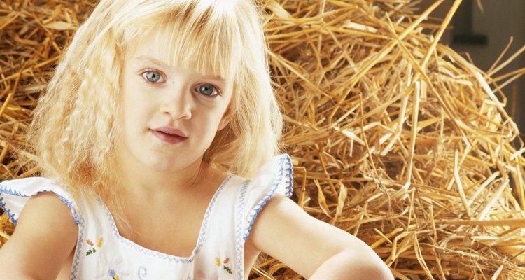 Girl (4-5) sitting by haystack, portrait