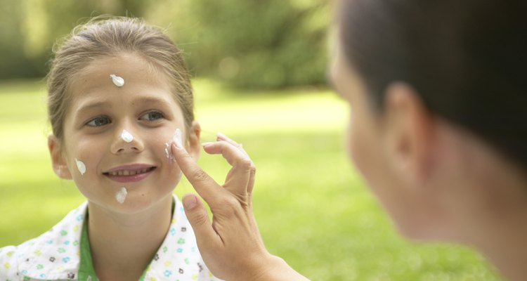 Mother applying sun lotion to daughter's (7-9) face, outdoors
