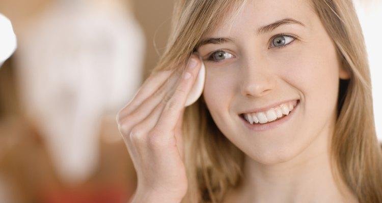 Teenage girl removing eye makeup