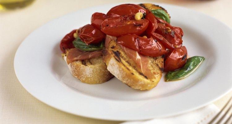 La albahaca fresca es comúnmente utilizada como hierba aromática en platos con tomate.