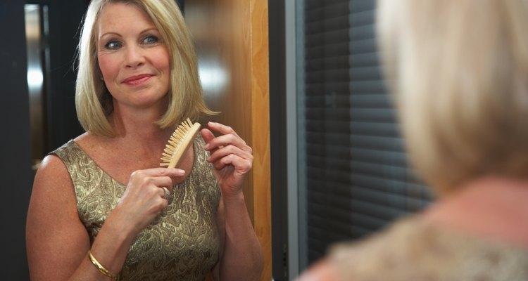 Woman brushing hair in mirror