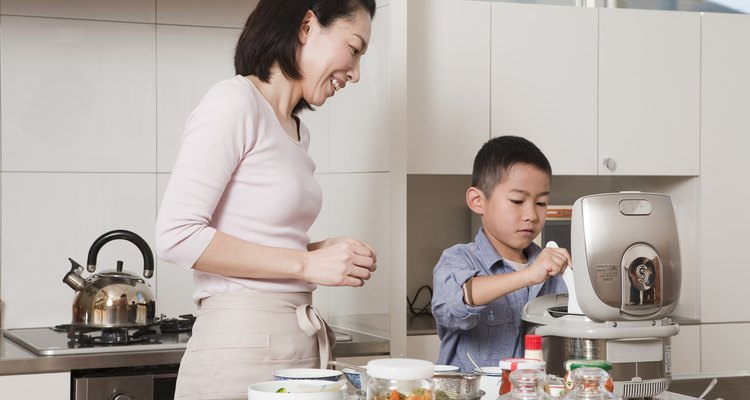 Mother and Son Serving Steamed Rice from Rice Cooker