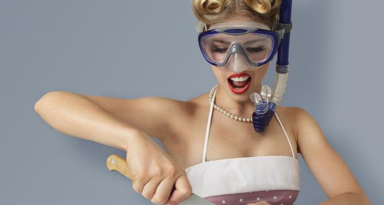 Una mujer corta cebolla con un equipo de buceo para evitar llorar mientras lo hace