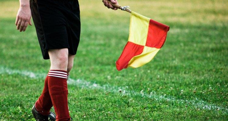 Da linha lateral, o bandeirinha auxilia o arbitro