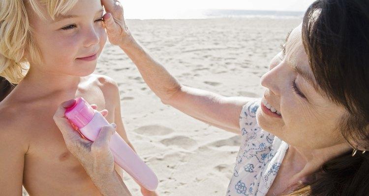 Woman applying sunscreen on boy