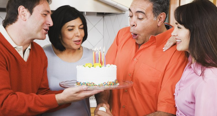 Middle-aged Hispanic man blowing out birthday candles