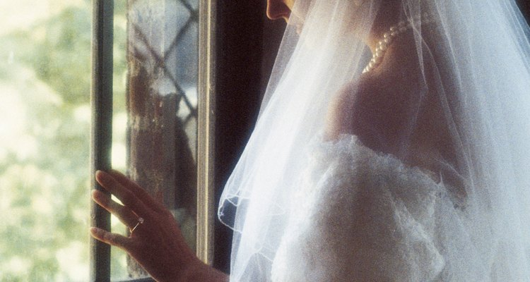 Woman in wedding gown looking out window of church