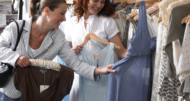 Two women examining dresses in clothes shop, laughing