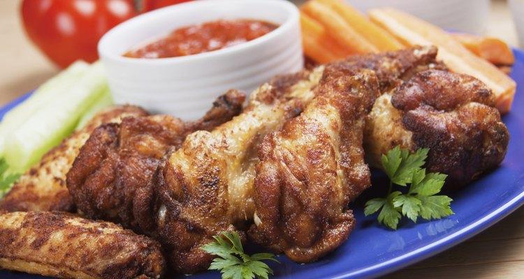 Alitas de pollo con acompañamiento de salsa y vegetales cortados.