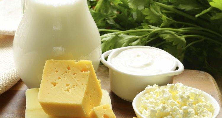 Produtos lácteos em uma tábua com ervas frescas