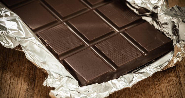 Dark chocolate bar in opened foil wrapping.