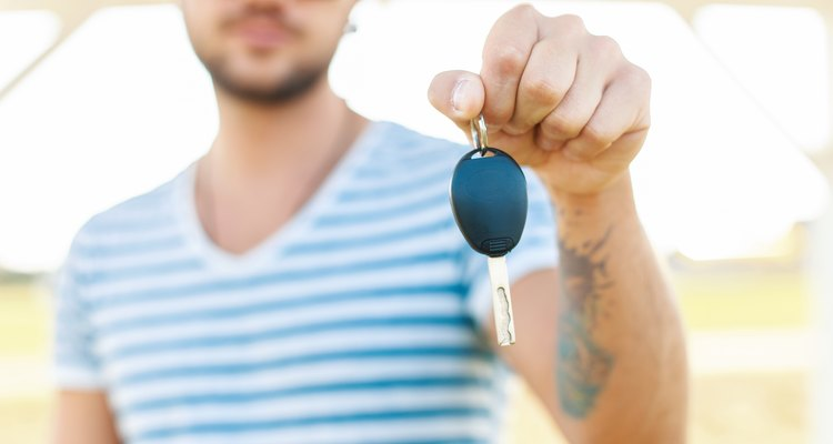 Young man holds the key to car rental