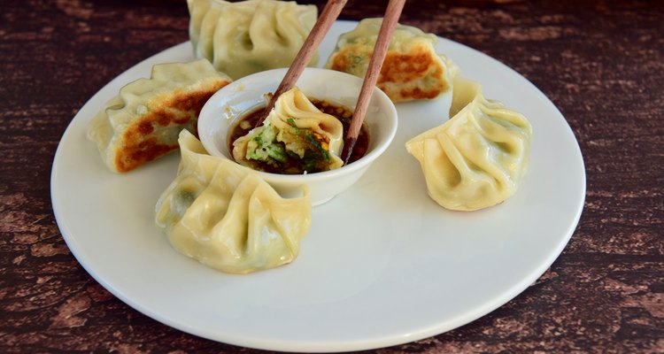 Plate of pot stickers with dipping sauce