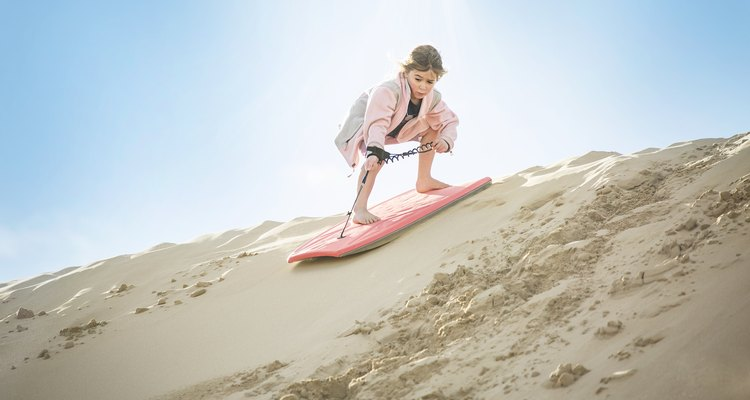 Little girl boarding down the desert sand dunes