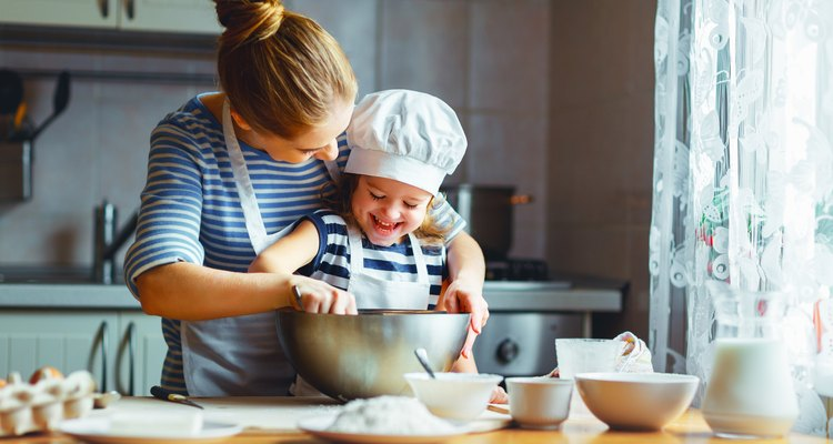 happy family in kitchen. mother and child preparing batter, bake cake